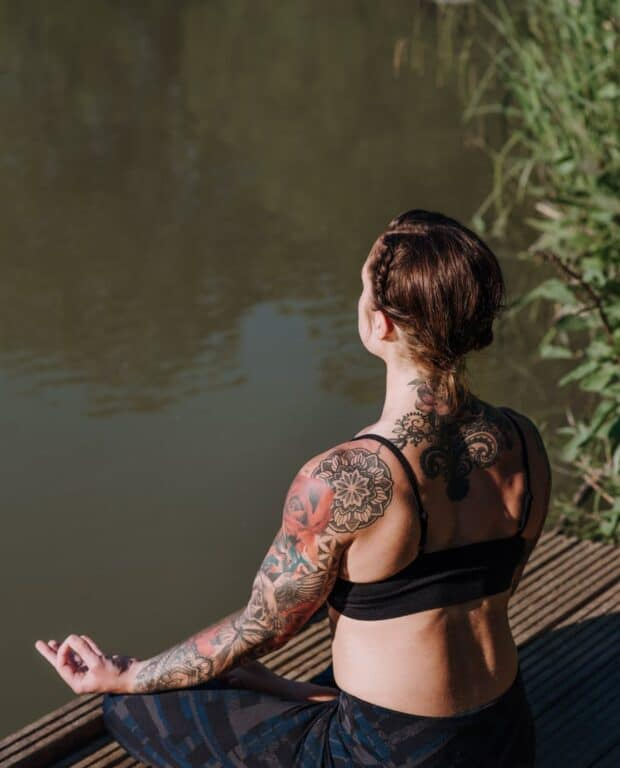unrecognizable tattooed woman meditating on dock against lake
